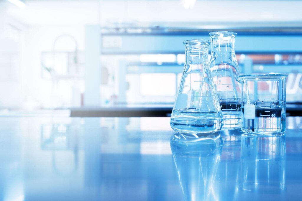 water in beaker and flask glass in chemistry science laboratory background
